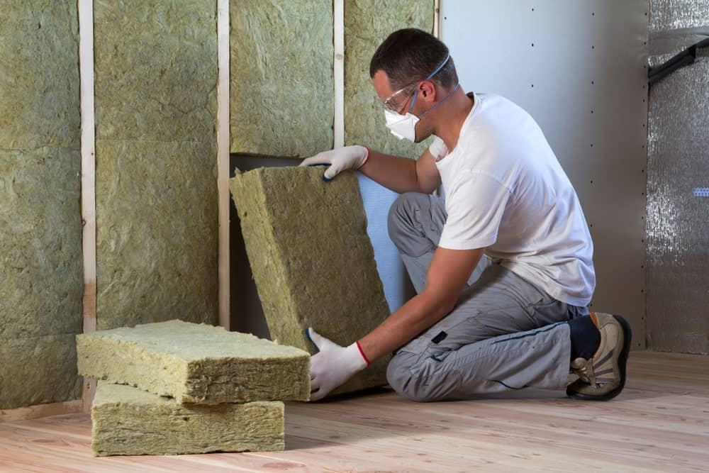 Man applying insulation on wall.