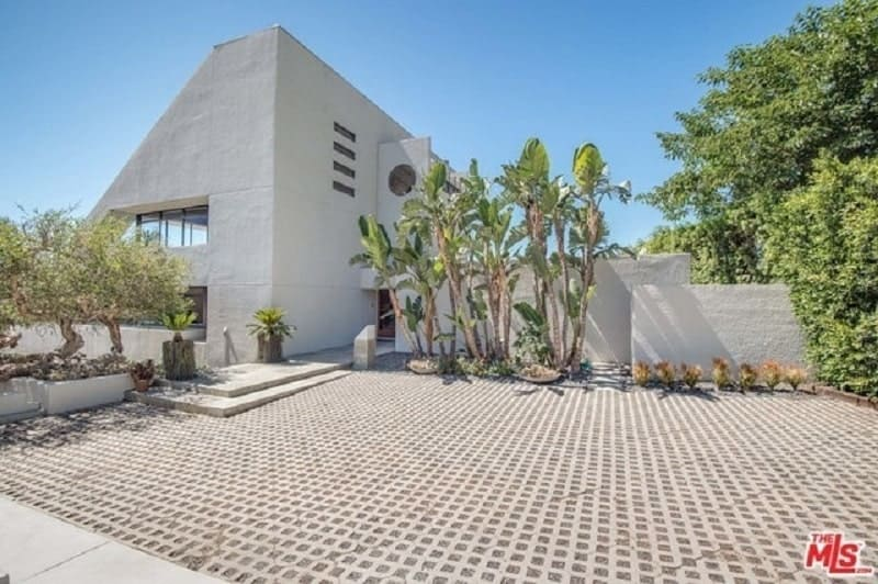 The irregular shape of the home gives it a unique look paired with the textured exterior white walls and glass windows. Its entry way is decorated by tall tropical trees along with some gnarled medium-sized trees and shrubs give it an aesthetic that is like no other.