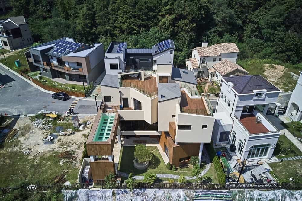Aerial view of this three-story house featuring an interesting rooftop architecture complemented with simple yet classy landscaping. Rainforest canopy trees served as a calming backdrop to the area.