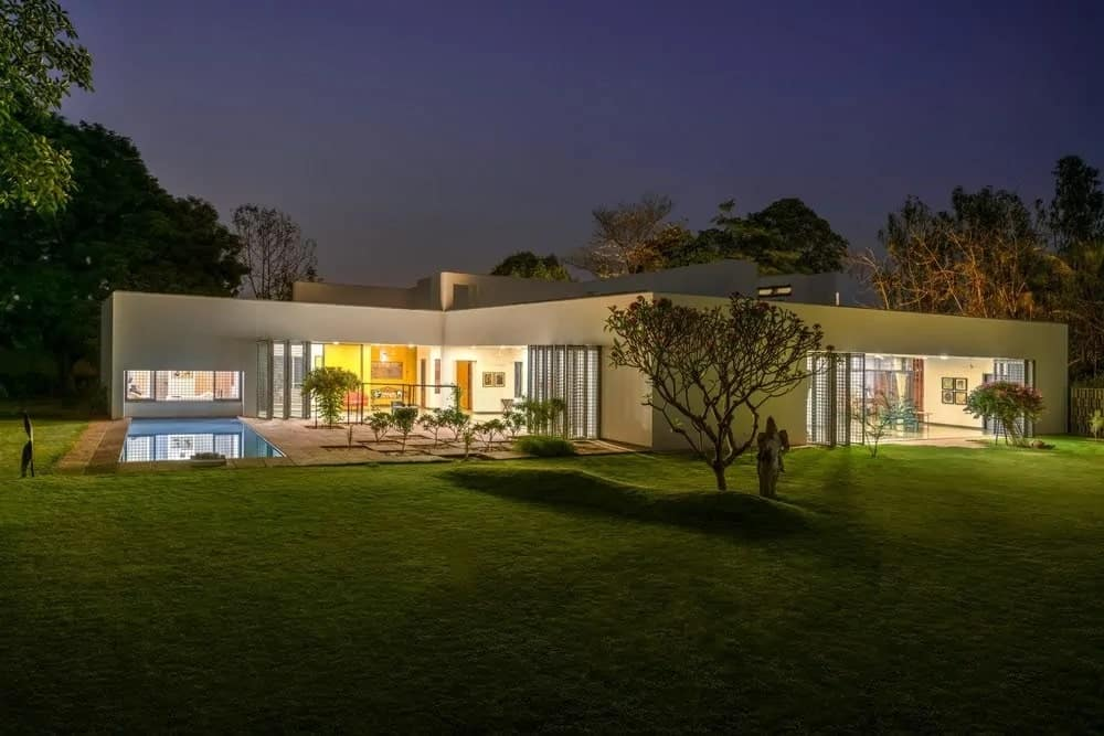 The simple and atypical home with white exteriors is complemented by the abundant interior lighting cascading to the the outdoor areas through wide opening walls with folding doors. These are then surrounded by a large lawn of grass and an outdoor pool.