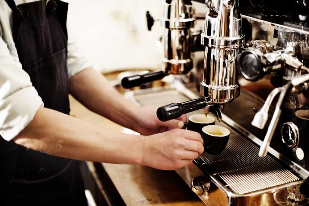 Barista holding two cups while coffee pours from a coffee grinder.