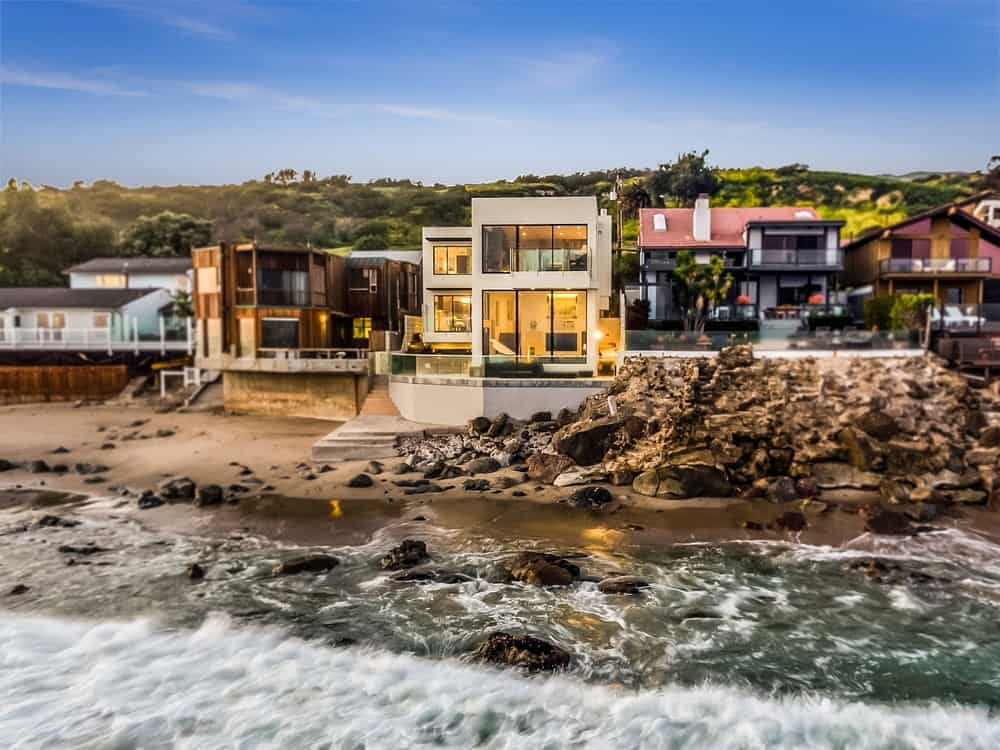 An outside view of Barry Manilow's famous Malibu beach house taken from the beach. It has a gorgeous modern exterior and a classy interior design.