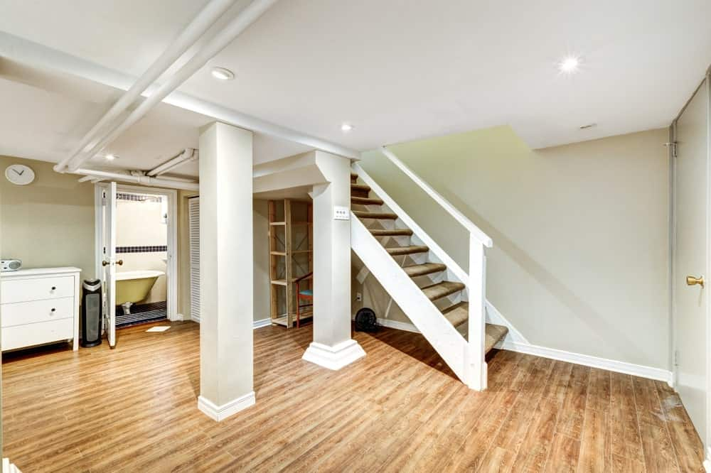 Spacious basement with staircase, bathroom, columns, exposed pipes and hardwood flooring.
