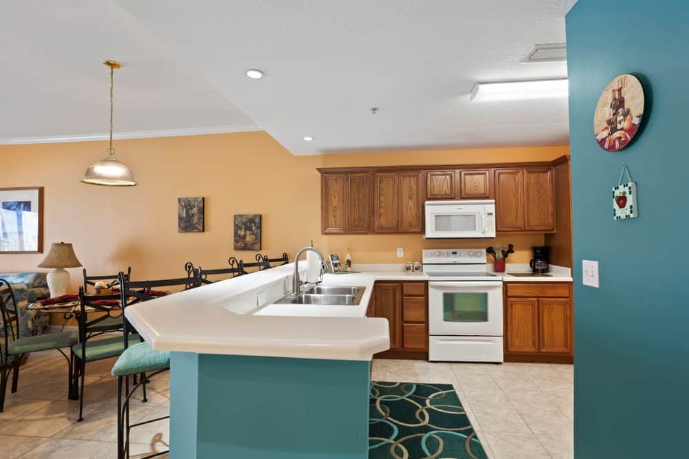 Beach-style eat-in kitchen with dark beige walls, marble tiled flooring, round dining set, teal peninsula, patterned rug, white appliances, dual undermount sinks and wooden cabinetry.