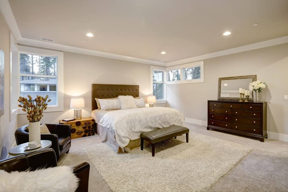 Beige master bedroom with tufted bed and bench, wooden dresser with rectangular mirror on top, chest trunk nightstands, carpet flooring, and sitting area showcasing leather round back chairs.