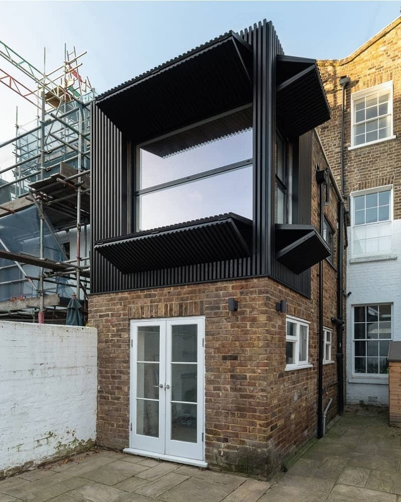 This small two-storey home has a charming quality to its red brick exterior walls and black metallic panels that fold to reveal tall glass windows. This completes a lovely Industrial-style aesthetic that partners with the concrete block walkway surrounding the home.