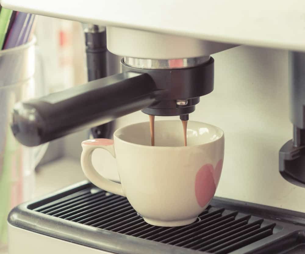 Professional coffee machine pouring espresso to a cup.