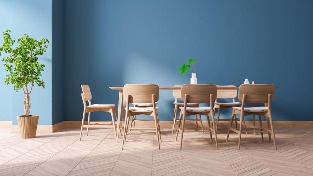 Blue dining room with parquet flooring, wooden dining table and matching chairs along with a tall potted plant on the side.