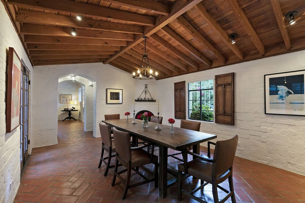 The home has a dining room as well, featuring a classy dining table and chairs set lighted by a fancy chandelier and has a corner fireplace. The room features a wooden vaulted ceiling with exposed beams. Images courtesy of Toptenrealestatedeals.com.
