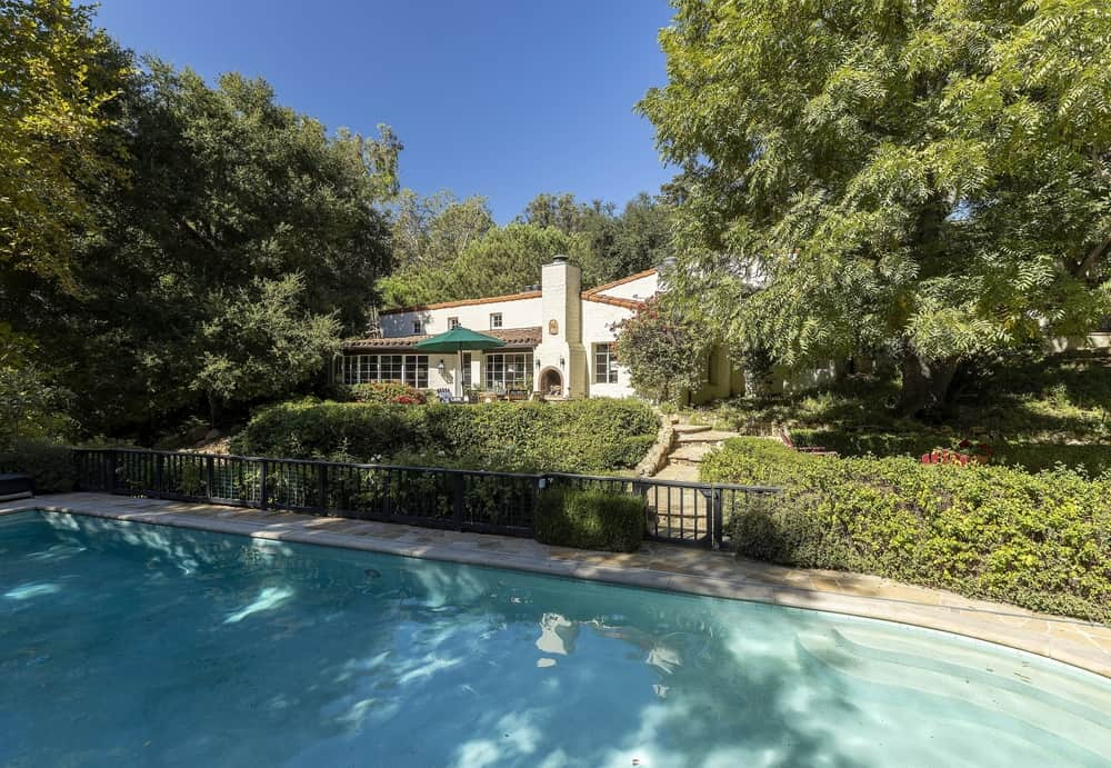 The property also boasts an outdoor swimming pool surrounded by the home's beautiful greenery. Images courtesy of Toptenrealestatedeals.com.