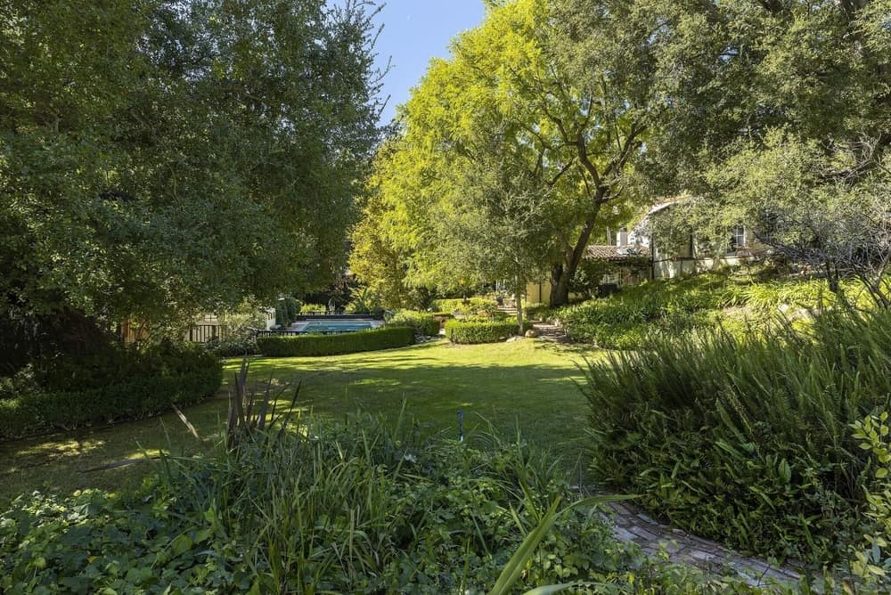 The property boasts a massive garden area featuring healthy lawn areas and green plants and trees. Images courtesy of Toptenrealestatedeals.com.
