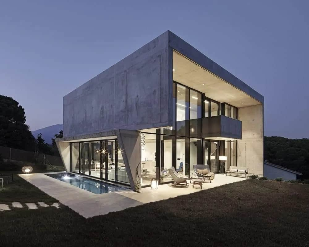 An amazing house with tall glass walls partnered with concrete walls brilliantly lit by the warm yellow exterior lights. This gives a warm cozy feel to the outdoor pool and sitting area just outside the glass walls and sliding doors surrounded by lawns of grass.