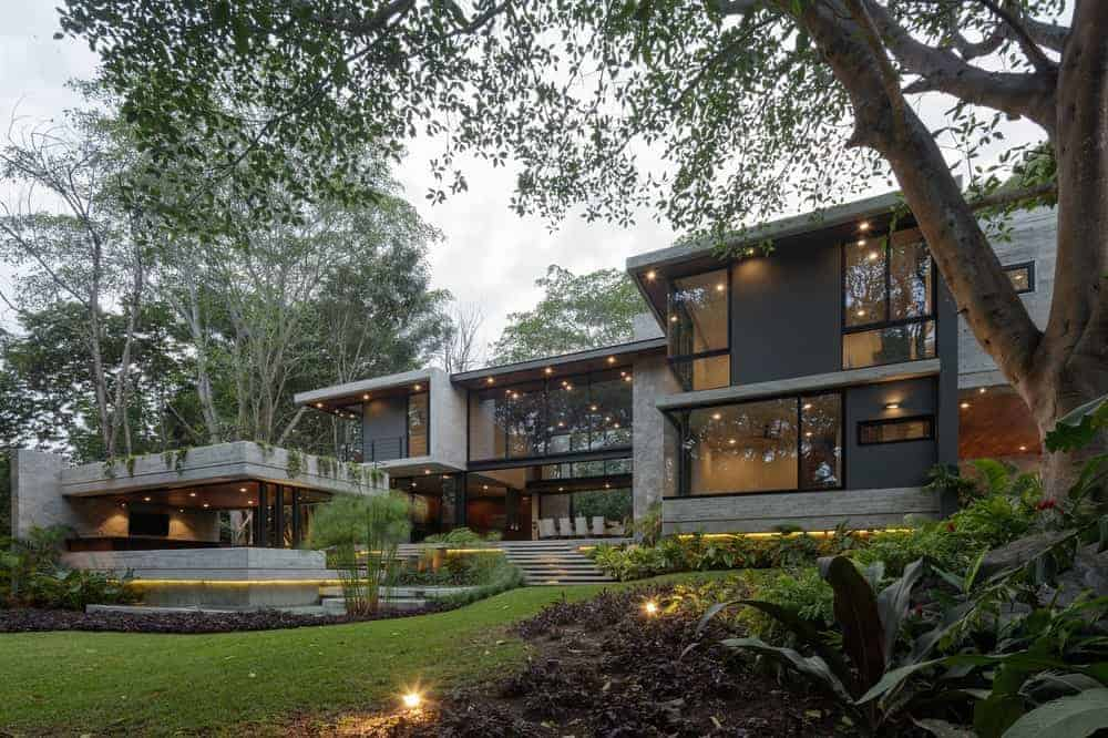Large contemporary house with a handsome-looking exterior featuring its glass walls and windows, along with its warm interior and exterior lighting.