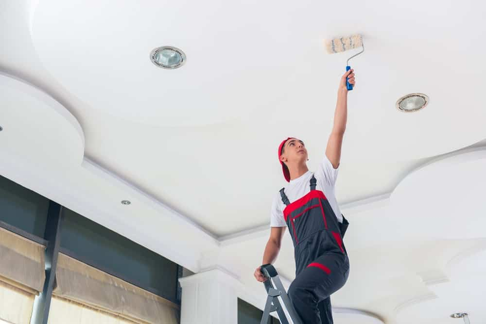 A painter on a ladder doing the ceiling using a roller.