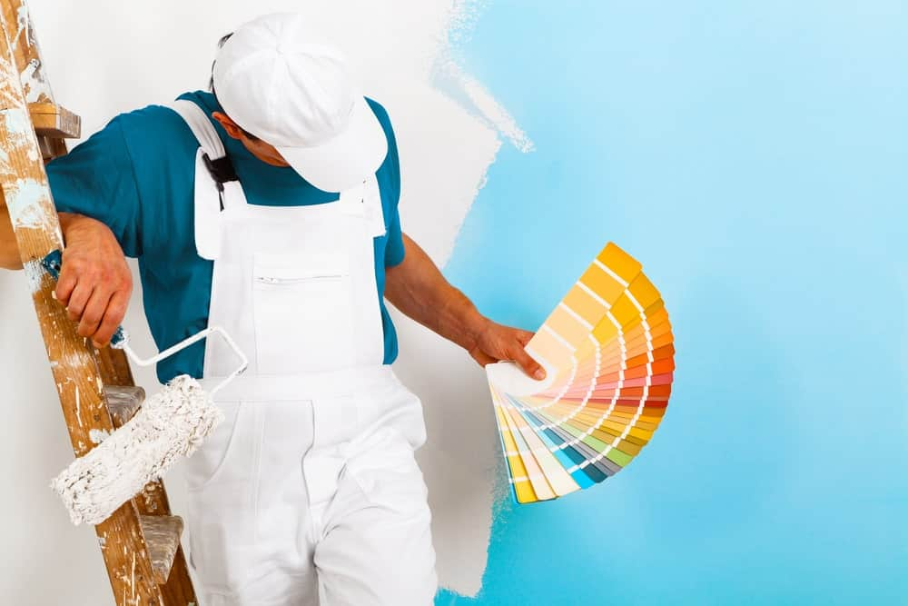 A painter picking colors from a set of swatches.