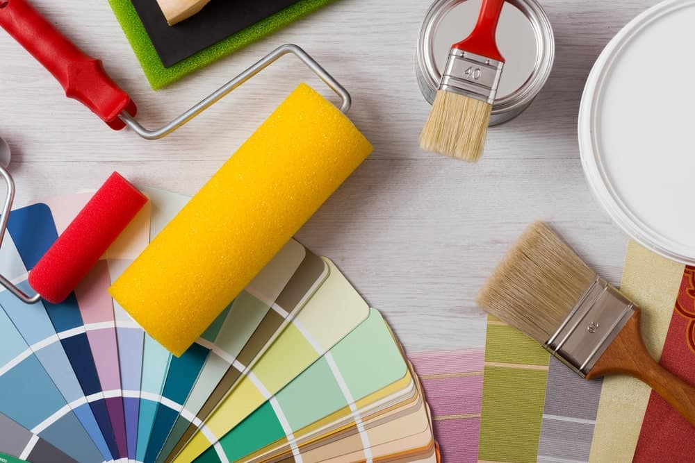 Rollers, brushes, cans of paint and color swatches on a wooden surface.