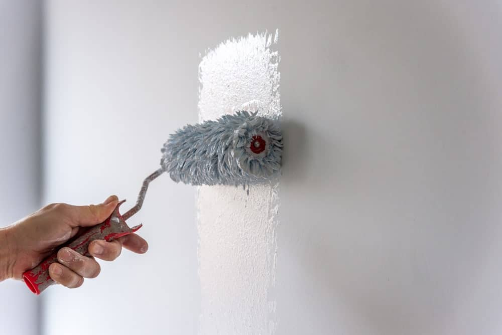 A wall being painted with white using a roller.