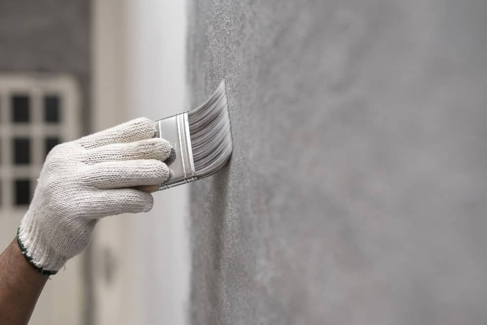 A worker painting the wall using a brush.