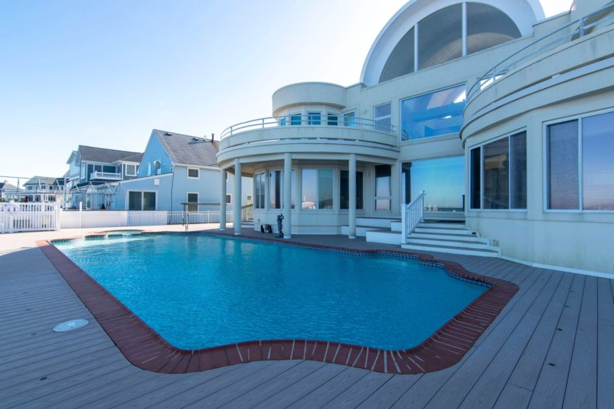 Luxurious mansion with a large open deck that's occupied by a swimming pool and an integrated jacuzzi.