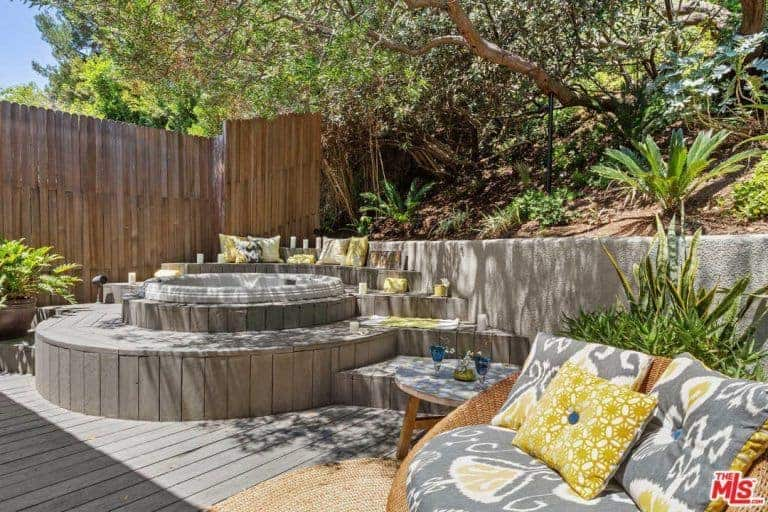 Light wooden deck with a touch of nature featuring tropical plants, bamboo fence and a cozy jacuzzi. It is completed with a comfy seat that's accented with printed cushions and <a class=