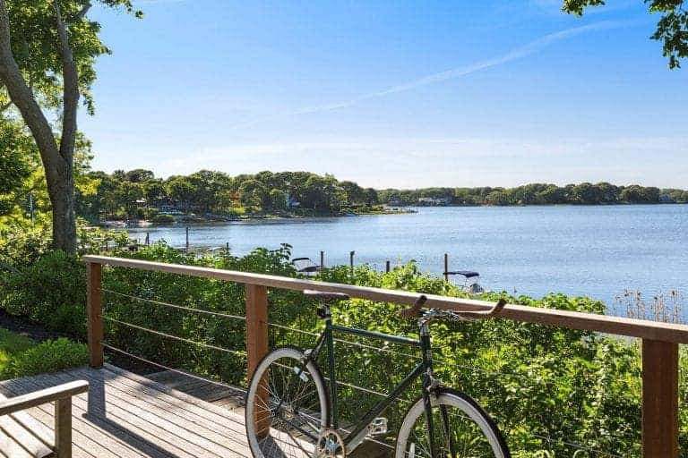 A relaxing deck with wide plank flooring and wooden railing overlooking the breathtaking waterfront of Sag Harbor. It is surrounded by grassy lawns and beautiful canopy trees.