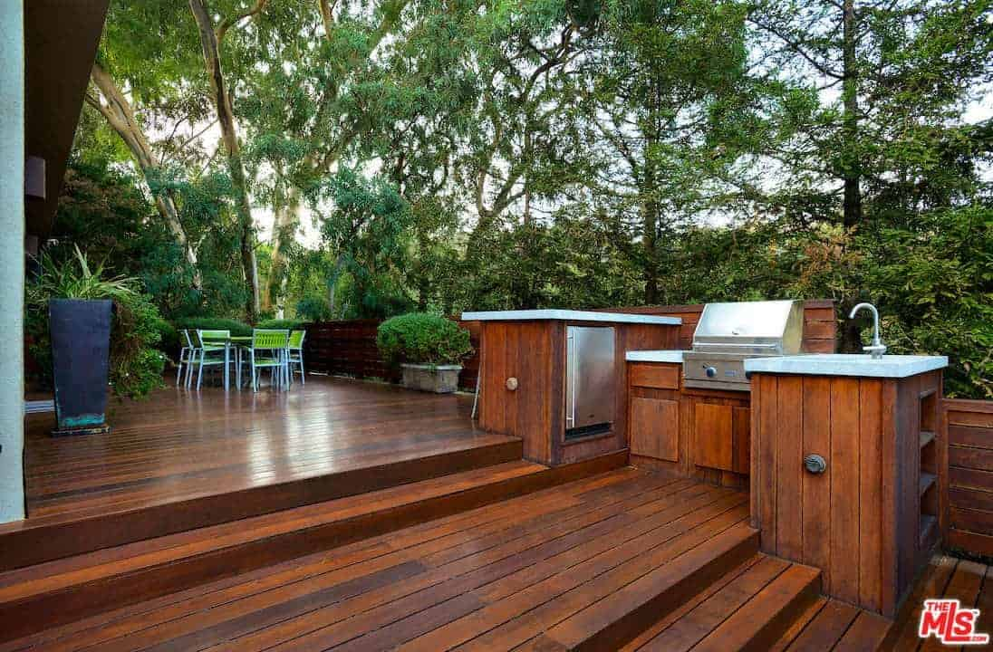 A spacious deck with redwood flooring matching with the counters and railings. It includes a green table and chairs that blend in with the surrounding.