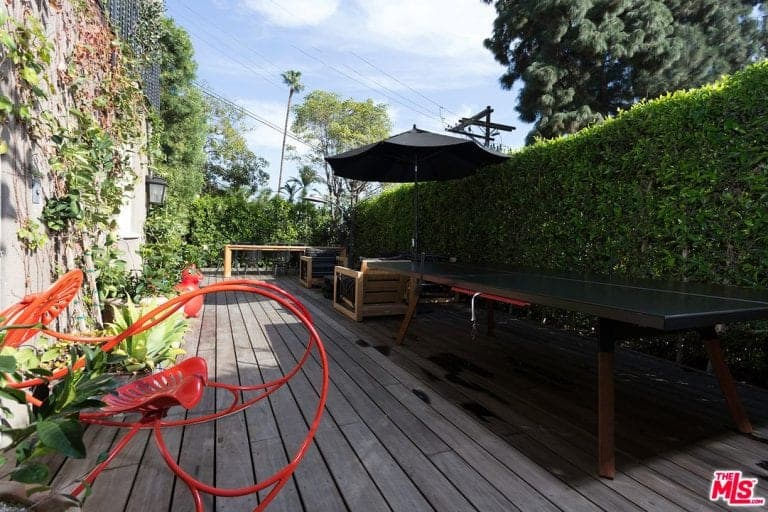 A unique red lounger stands out in this relaxing deck that's filled with a long table and wooden seats under a freestanding umbrella. It is sandwiched by a hedge plant and concrete fence that's covered with creeping plants.