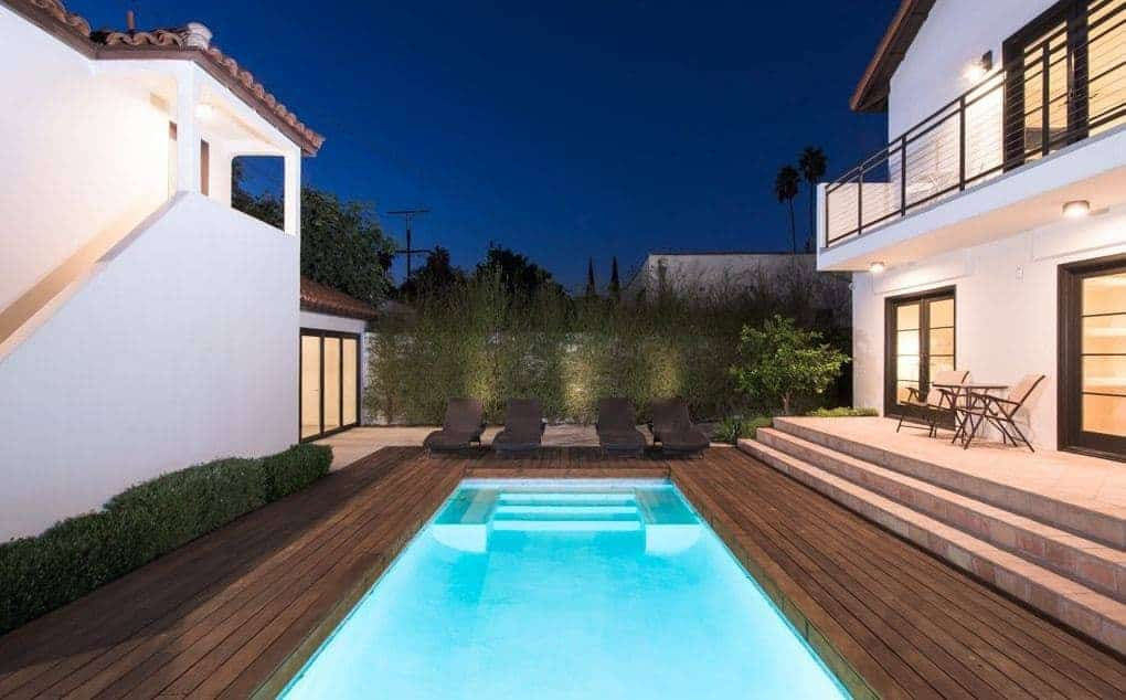 Simple but incredible deck with black loungers facing the stunning swimming pool that almost fills up the area. Manicured shrubs and tall plants completed the look.