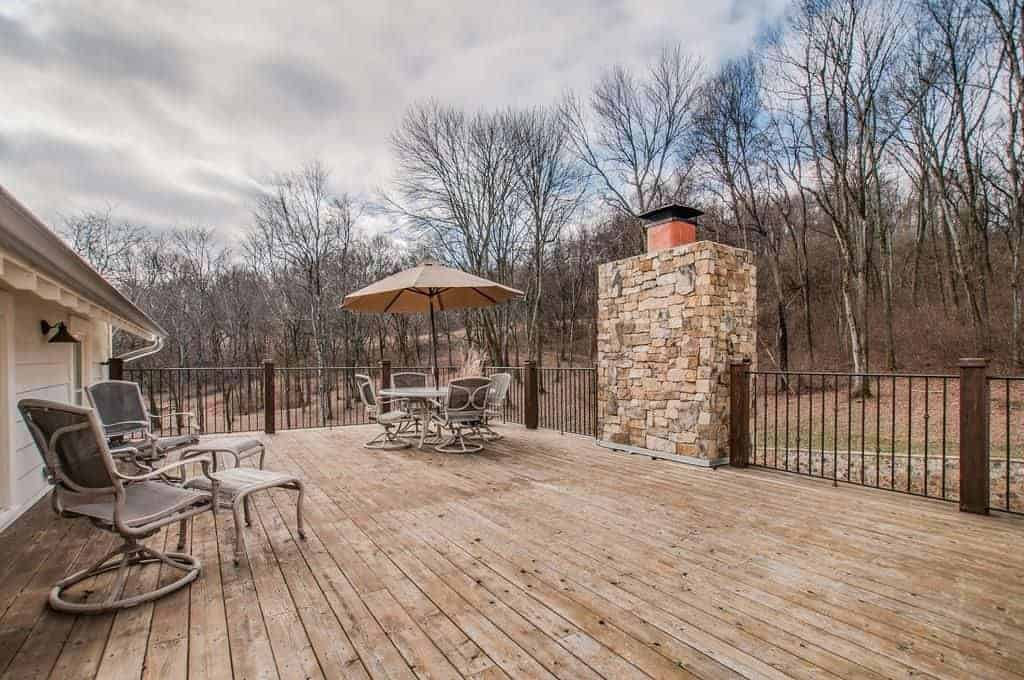 An open deck with a country vibe showcasing wooden flooring and metal railing accented by a stone brick pillar. It is filled with multiple seating while overlooking the expansive property.