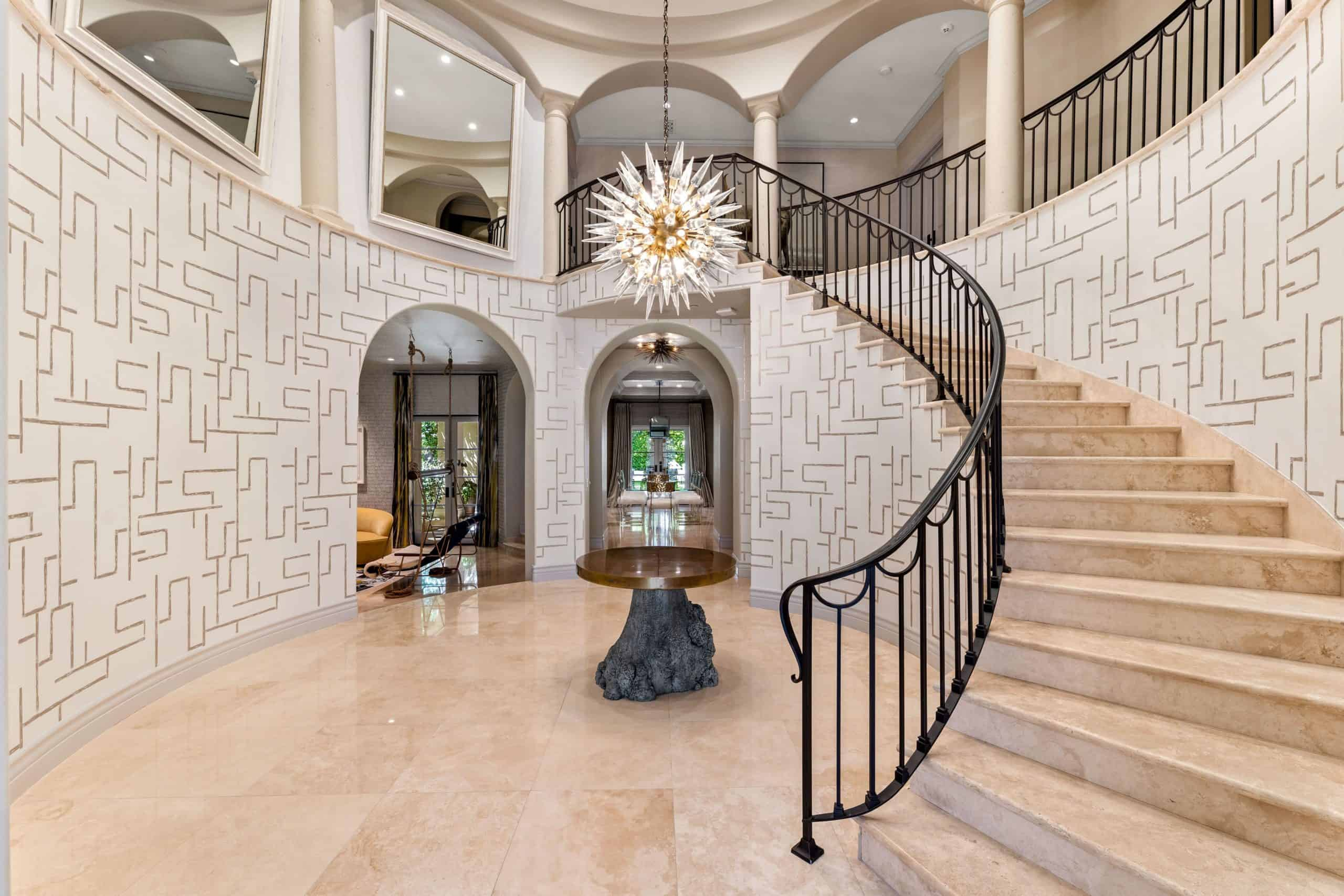 A grand foyer boasting elegant walls, beige tiles floors and a two-storey ceiling. The area has a charming centerpiece table with a stunning chandelier set just above it and a curved staircase.