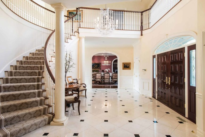 A gorgeous foyer boasting classy tiles flooring and a two-storey ceiling with a fancy chandelier hanging from it. There's a curved staircase with carpeted steps.