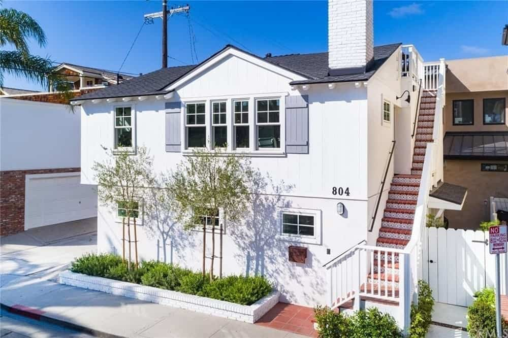 This is a brilliant white two-storey home with lovely tinted windows to complement the uniform white exterior walls as well as a small planter in front by the sidewalk with shrubs and tall thin trees. On the side of this home is a set of steps that can lead to the second level and the rooftop.