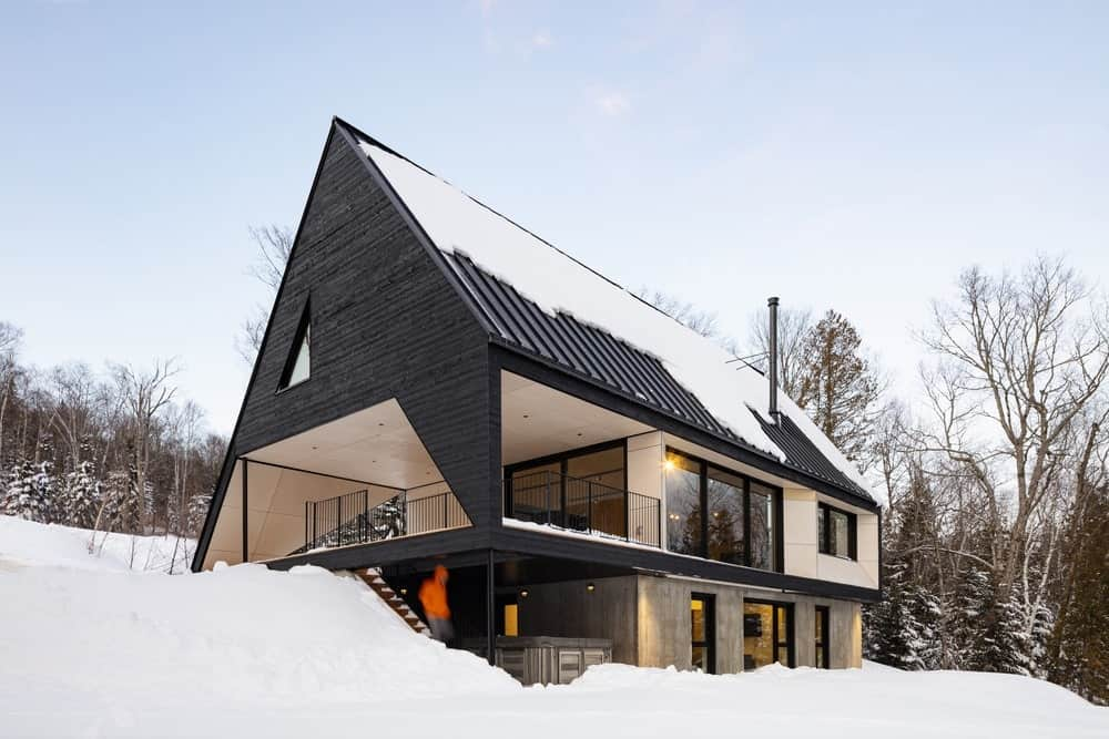 This house boasts a stylish black exterior with a stunning roof design. The grounds are covered in snow.