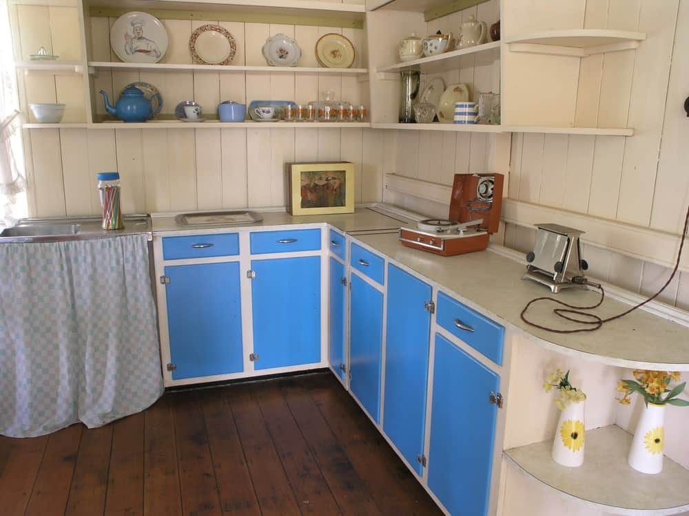 1960's kitchen with beadboard walls, hardwood flooring, floating shelves, blue cabinets and an undermount sink.