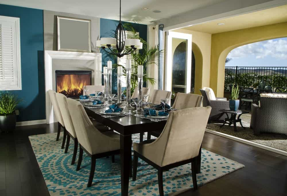 Dining room with blue walls, dark wide plank flooring, a fireplace, rectangular dining table with beige cushioned chairs, contemporary chandelier, printed rug and sliding door that opens to the balcony overlooking the outdoor scenery.