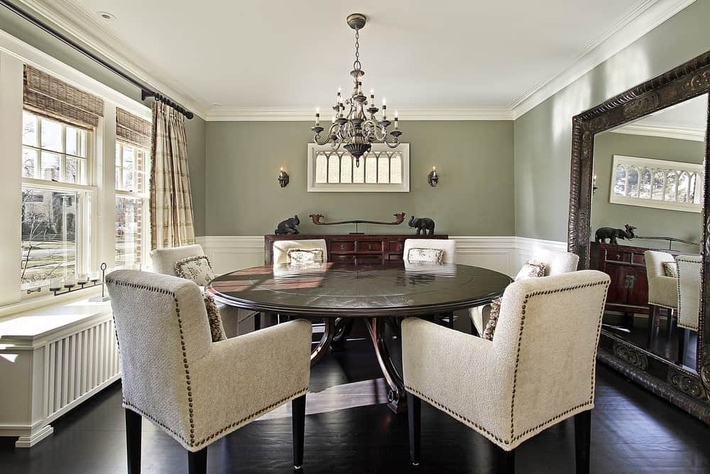 Luxury dining room with a large antique mirror, white framed windows covered in wicker shades, sage green walls, dark hardwood flooring, round dining table paired with beige upholstered chairs, candle chandelier, white wainscoting and crown molding.