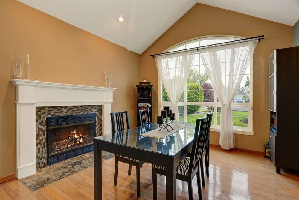 Dining room with vaulted ceiling, mustard walls, hardwood flooring, dark wood dining table with matching cushioned chairs and an arched window covered in white sheer curtains.