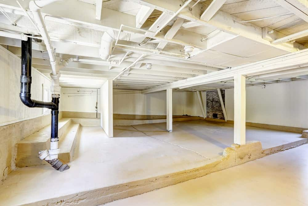 Empty basement with concrete flooring, beamed ceiling, wood columns and exposed pipes.