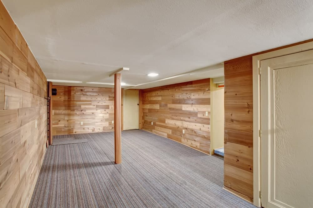 Empty basement room with wood plank walls, carpet flooring and white textured ceiling..
