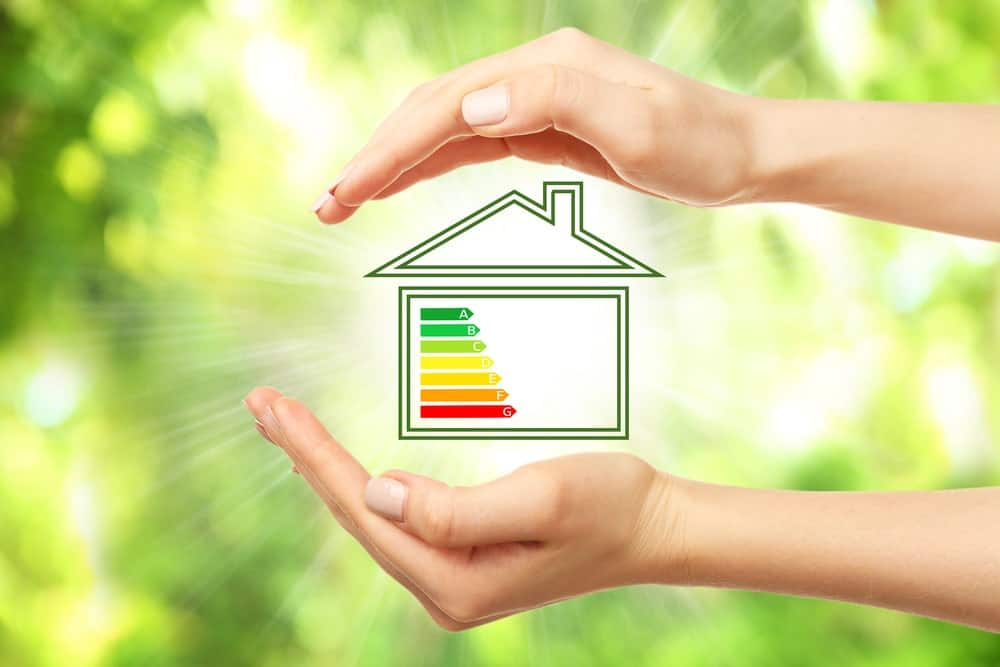 A house with energy efficiency scale image in the middle of a woman's hands.