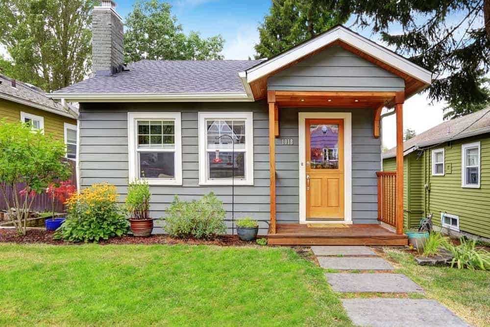 A quaint small grey wooden house with a wooden front deck and a front yard with hedges, grass lawn and concrete walkway.