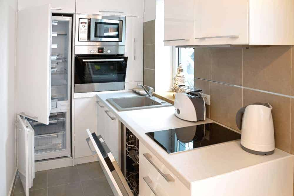 A small modern white kitchen with modern appliances, earthy beige backsplash tiles and gray floor tiles.