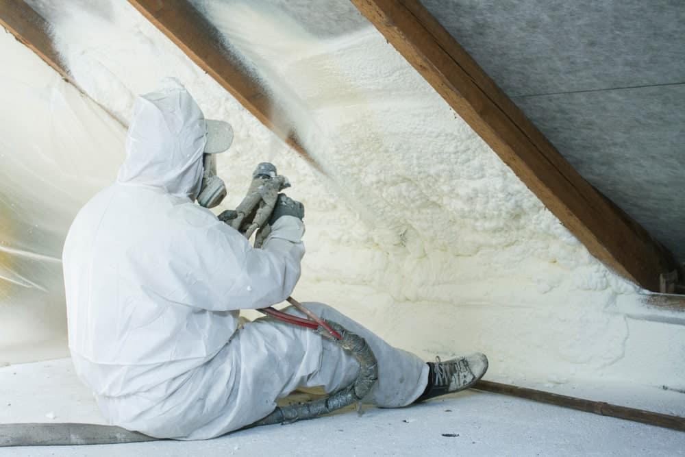Technician spraying foam insulation using plural component gun for polyurethane foam.