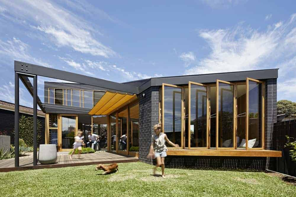 A fancy house finished in black, designed by BENT Architecture. It's a stylish contemporary house with glass windows and doors. The lawn area is just perfect for kids and pets.