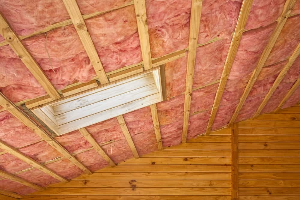 Fiberglass insulation installed in the sloping ceiling of an attic.