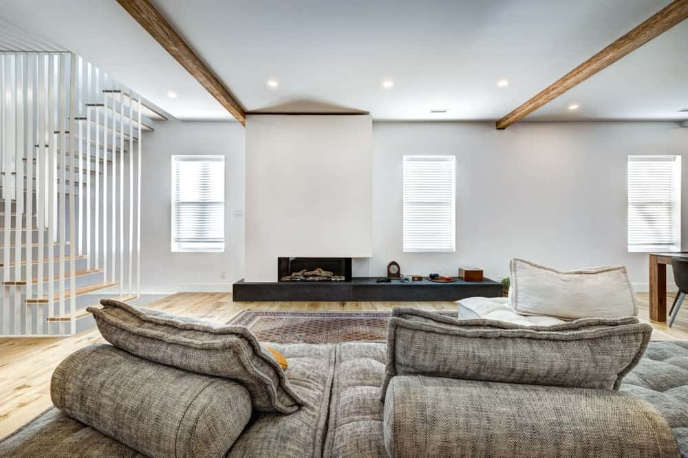 Minimalist basement with white walls, tufted L-shaped sofa, fireplace, hardwood flooring and recessed lights fitted on the wood beamed ceiling.