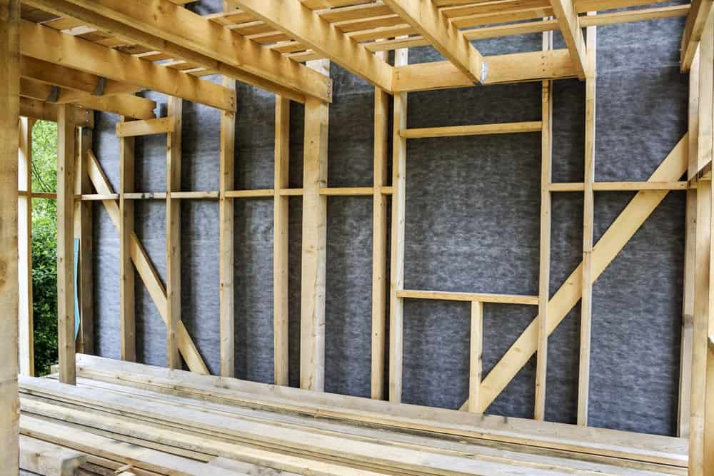 Framework of the house wall installed with a gray vapor barrier.