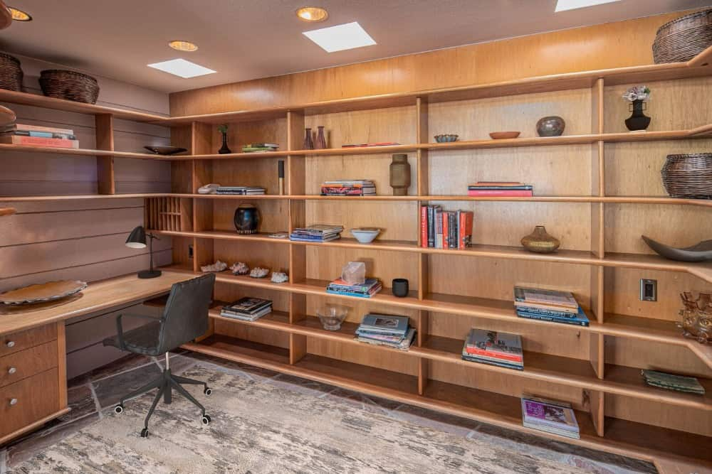 The home office offers multiple shelving and a built-in desk paired with a modern chair. Images courtesy of Toptenrealestatedeals.com.