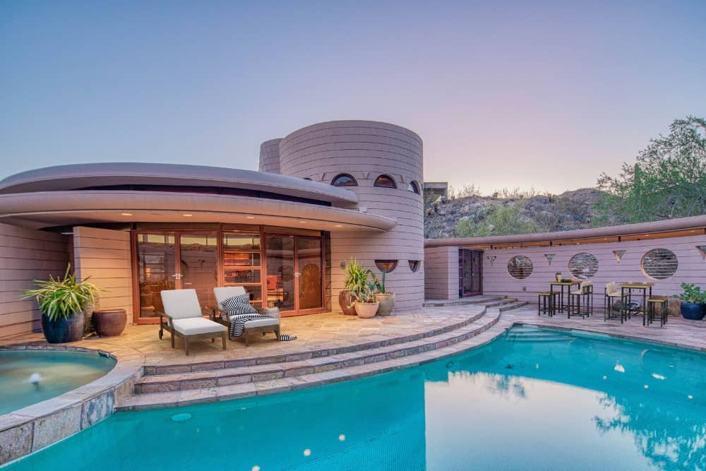 The outdoor area boasts a large custom swimming pool with sitting lounges and some tables with bar stools. Images courtesy of Toptenrealestatedeals.com.