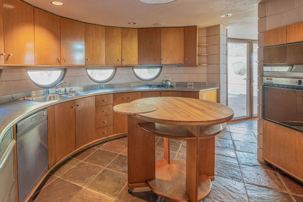 The kitchen has a curved kitchen counter and has a small round center island. Images courtesy of Toptenrealestatedeals.com.